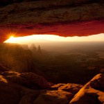 Rock arch with sun and canyon.   Canyonlands National Park, Moab, Utah.