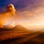 Mt. Bromo volcano erupting with strong god rays in the foreground.  Bromo, East Java, Indonesia.