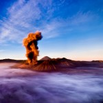 Mt. Bromo volcano erupting in the early morning with fog filling the area around it.   Mt. Bromo, East Java, Indonesia.